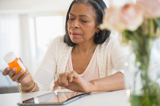 older woman holding prescription bottle and looking at tablet